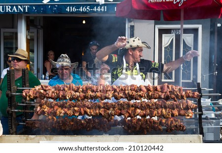 TORONTO, CANADA - 10 AUGUST 2014: A man dancing behind a food stall during the Taste of Danforth Street Festival - stock photo