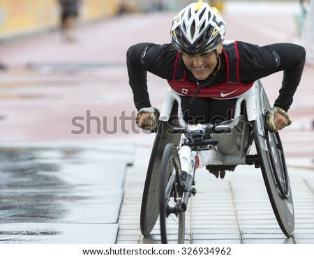 TORONTO,CANADA-AUGUST 8,2015:Canadian wheelchair racing athlete moving off the track in her wheelchair after the race at the 2015 Parapan American Games. Case # 01953074 - stock photo