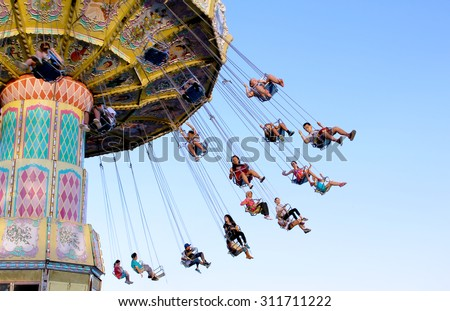TORONTO, CANADA - AUGUST 25, 2014: Swing ride at Canadian National Exhibition in Toronto, Ontario, Canada. CNE is largest annual fair in Canada and the seventh largest in North America. - stock photo
