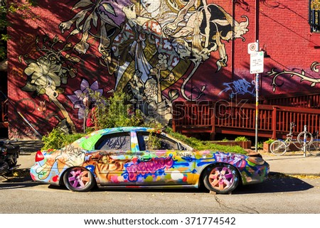 TORONTO,CANADA 16-10-2015:Graffiti Car in front of Big Fat Burrito restaurant in the Pedestrian Sundays celebration in Kensington Market. Kensington Market is a distinctive multicultural neighborhood - stock photo