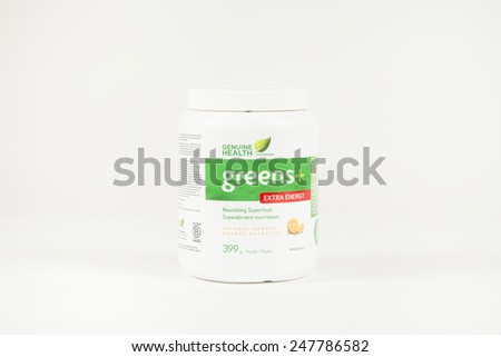 Toronto, Canada - January 27 2015 : A plastic container of Greens+ Powder of the Extra Energy Variety produced by Genuine Health shown on a bright background - stock photo