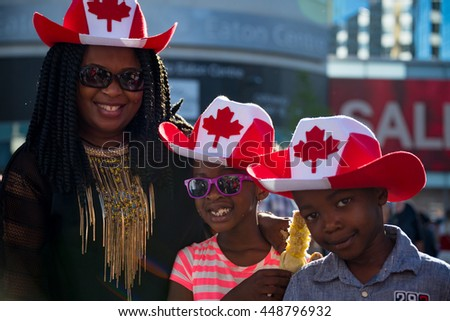 TORONTO,CANADA-JULY 1,2016:Canada Day people: Afro American family enjoying the 149th Canada Day celebration..Canada Day  is the national day of Canada and a federal statutory holiday - stock photo