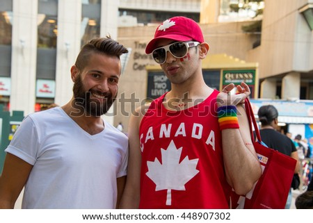 TORONTO,CANADA-JULY 1,2016: Canada Day people: Gay men couple enjoying in Nathan Phillips Square.Canada Day  is the national day of Canada and a federal statutory holiday. - stock photo