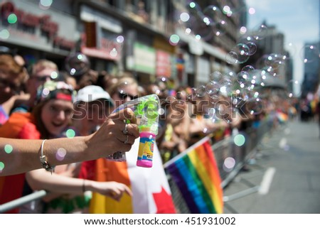 TORONTO,CANADA-JULY 3,2016: 2016 Pride Parade: Man using bubble gun behind barricades. Torontonians gathered on the street celebrating 36th Pride Parade with the LGBT community.