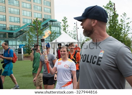 TORONTO,CANADA-JUNE 20,2015: Canadian Trampoline gymnast, Rosannagh MacLennan carries the Toronto 2015 Pan Am games torch, escorted by the policeman.