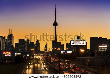 TORONTO,CANADA-JUNE 24,2015: Cityscape of Toronto at dusk. Dark. Skyscrapers and billboards visible in the orange twilight and trailing lights of the vehicles moving on the road. - stock photo