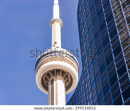 TORONTO,CANADA-JUNE 15,2015: Close-up of CN tower and condo Building against blue sky. The CN Tower is the world's 6th tallest free-standing structure - stock photo
