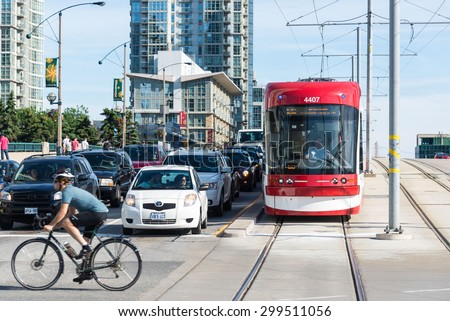 TORONTO,CANADA-JUNE 15,2015: Cyclist passing by a traffic junction as cars and a tram wait for the signal to turn green. Vehicles stopped at the traffic signals awaiting their turn. - stock photo