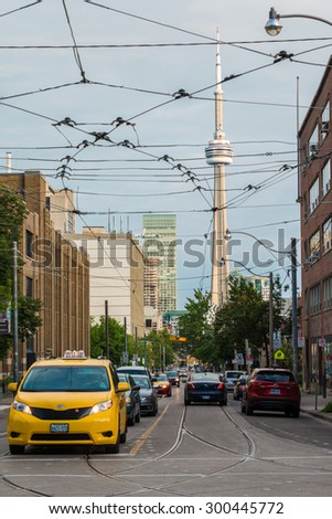TORONTO,CANADA-JUNE 16,2015: Streetcars wiring with CN tower in background. Central street of Toronto during the day with cars traffic. CN TV Tower on the background. - stock photo