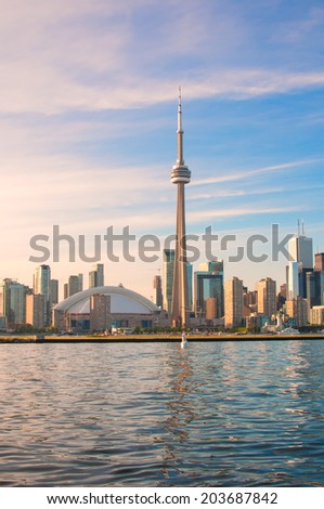 TORONTO, CANADA - JUNE 7, 2014: View of the CN Tower and Rogers Center, opened in 1989 as the home of Toronto Blue Jays and is the first to have retractable motorized roof. - stock photo