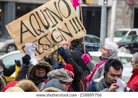 TORONTO,CANADA-MARCH 8,2015: Aquino resign sign.Thousands gathered in Toronto to mark International Women Day IWD with a protest march demanding improvements in many social issues. - stock photo