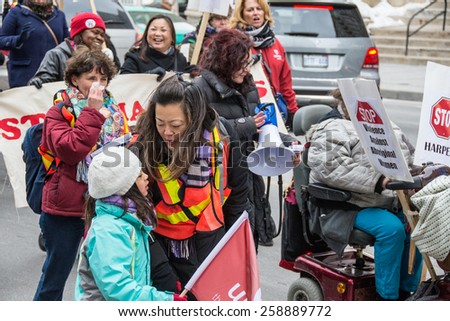 TORONTO,CANADA-MARCH 8,2015: Jenny Ahn from Unifor.Thousands gathered in Toronto to mark International Women Day IWD with a protest march demanding improvements in many social issues. - stock photo