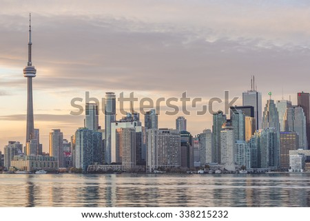 TORONTO, CANADA - NOVEMBER 02, 2015: Downtown Toronto skyline with the CN Tower apex and the Financial District skyscrapers - illuminated at sunset. - stock photo