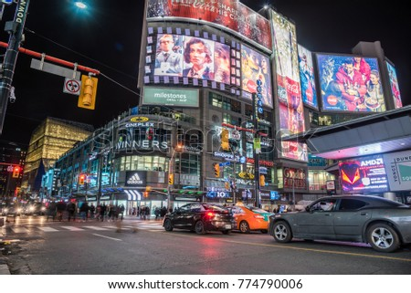 Toronto, Canada - November 18, 2017:  People Crossing a Pedestrian Scramble in Yonge-Dundas Square at Night. The intersection is one of the busiest in Canada, serving over 100,000 pedestrians daily.