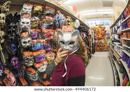 TORONTO,CANADA-OCTOBER 2, 2016:Lady trying on a scary mask in a store. Halloween products inventory in shop. Halloween is a popular festivity in Canada