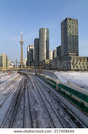 TORONTO, CANADA - 26TH FEBRUARY 2015: GO Trains in downtown Toronto during the winter. Condos and the CN Tower can be seen - stock photo