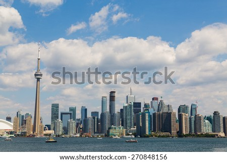 TORONTO, CANADA - 6TH JULY 2014: Toronto Skyline during the summer, showing buildings, the CN Tower and boats in the water. - stock photo