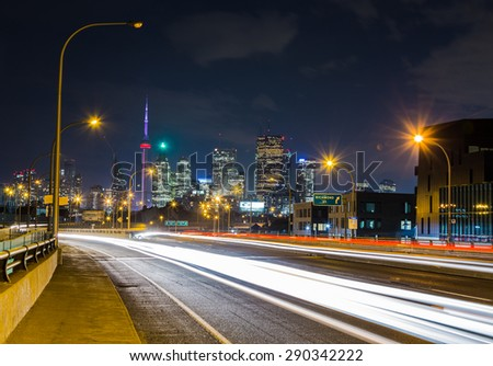 TORONTO, CANADA - 18TH JUNE 2015: Downtown Toronto viewed from the Lake Shore Boulevard East road. The trails of cars can be seen going past. - stock photo