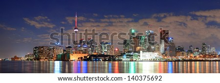 Toronto cityscape panorama at night over lake with colorful light.