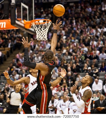 TORONTO - FEBRUARY 16: Dwyane Wade (C) participates in an NBA basketball game at the Air Canada Centre on February 16, 2011 in Toronto, Canada.  The Miami Heat beat the Toronto Raptors 103-95. - stock photo