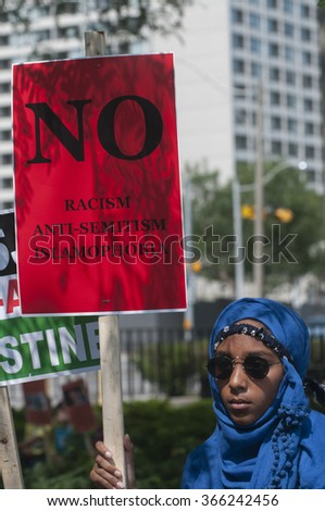 TORONTO-JULY 11: A Muslim women holding a sign urging to decline the concept of racism and Islamophobia  during the Al-Quds day rally on July 11, 2015 in Toronto,Canada. - stock photo