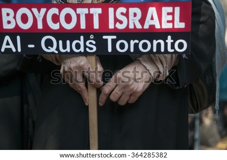 "TORONTO-JULY 11:  A Muslim women wearing Burkha with a sign asking to ""boycott Israel""  during the Al-Quds day rally on July 11, 2015 in Toronto,Canada."