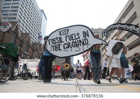 "TORONTO - JULY 5 : Participants with ""stop the usage of fossil fuel"" signs  during the Jobs,Justice and Climate rally on July  5, 2015 in Toronto, Canada."
