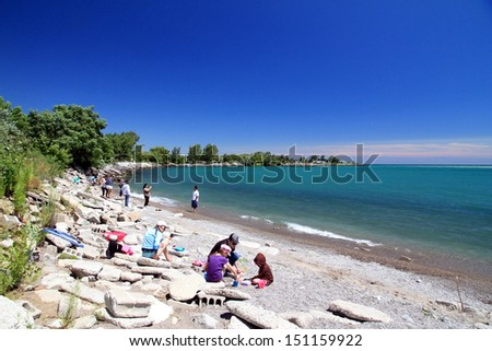 TORONTO - JULY 27: People on a beach on the Lake Ontario on July 27, 2013 in Toronto. Lake Ontario is the easternmost of the Great Lakes and the smallest in surface area (7,340 sq mi, 18,960 km2).