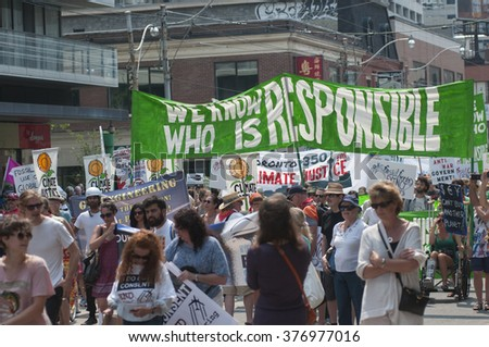 "TORONTO - JULY 5 : People walking under a big banner which says ""we know who is responsible"" during the Jobs,Justice and Climate rally on July  5, 2015 in Toronto, Canada."