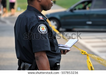 TORONTO-JULY 17: Toronto policeman taking notes at the crime scene where shooting leaves 2 dead and 21 injured on July 17, 2012 in Toronto - stock photo