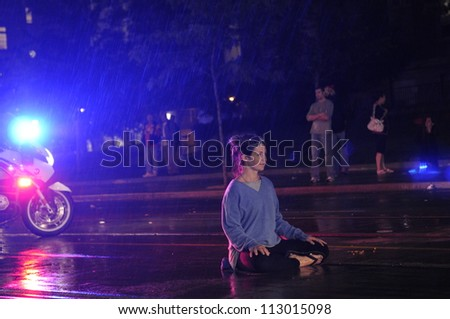 TORONTO-JUNE 26:  A peaceful protester meditating on the streets while being watched closely by a  officer on his bike  during the G20 Protest on June 26, 2010 in Toronto, Canada.
