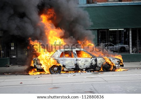 TORONTO-JUNE 26:   A police car burning after being torched by the protesters during the G20 Protest on June 26, 2010 in Toronto, Canada. - stock photo