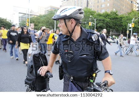 TORONTO-JUNE 28: A police officer guiding a rally during the G20 Protest on June 28, 2010 in Toronto, Canada. - stock photo