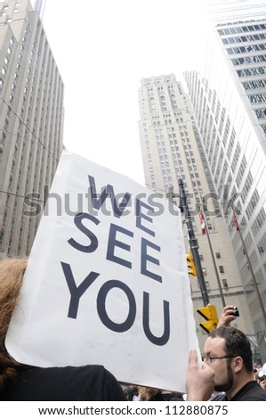 "TORONTO-JUNE 27:   A protester carries a sign saying ""we see you"" so as to warn the financial institutions  during the G20 Protest on June 27, 2010 in Toronto, Canada."