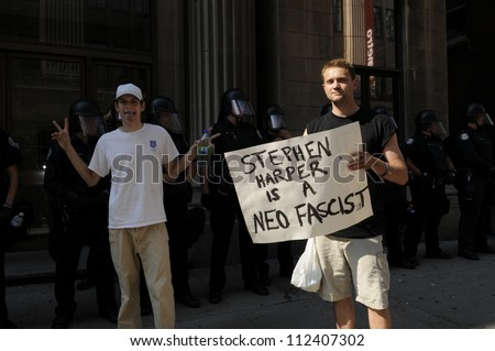 TORONTO-JUNE 25:  A protester holding a banner saying the Prime Minister of Canada is a fascist while another one makes  a funny face during the G20 Protest on June 25, 2010 in Toronto, Canada. - stock photo