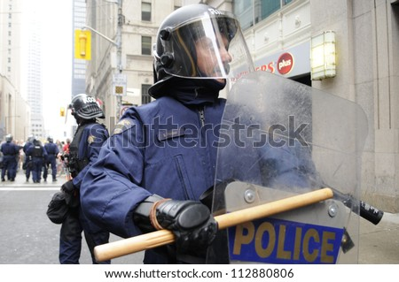 TORONTO-JUNE 26:  A riot police officer hitting his riot shield with his baton during the G20 Protest on June 26, 2010 in Toronto, Canada. - stock photo