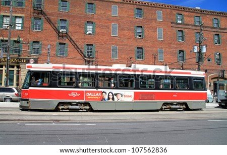 TORONTO - JUNE 29, 2012: A streetcar in a city street on June 29, 2012 in Toronto. The Toronto Transit Commission (TTC) operates 11 streetcar lines and 248 streetcars. - stock photo