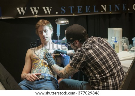 TORONTO - JUNE 19 :  A tattoo artist working closely on a tattoo on his clients chest during the Toronto Tattoo convention on June 19, 2015 in Toronto, Canada.