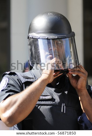 TORONTO-JUNE 25:  A Toronto Police  officer fixing his helmet during  the G20 Protest on June 25, 2010 in Toronto, Canada. - stock photo