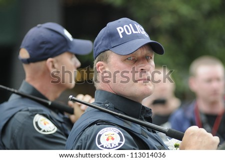 TORONTO-JUNE 26:  A visibly angry police officer looking for suspects after one of the police car was torched during the G20 Protest on June 26, 2010 in Toronto, Canada. - stock photo