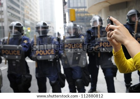 TORONTO-JUNE 26:  A woman with her mobile phone taking pictures of the protesters during the G20 Protest on June 26, 2010 in Toronto, Canada. - stock photo