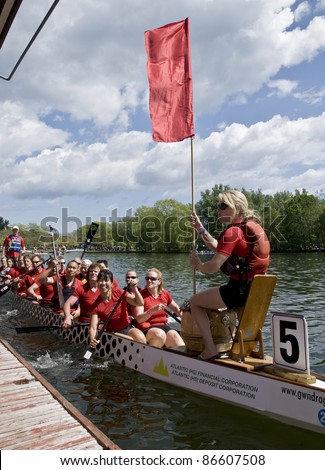 TORONTO - JUNE 21: ADBCCSDC Alliance Boat Dragon's Dragon Boat holding a flag in the Final of the Toronto International Dragon Boat Racing Festival. - stock photo