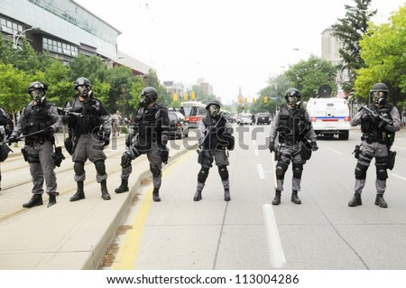 TORONTO-JUNE 27:  Elite  police personnel with gas masks protecting the streets during the G20 Protest on June 27, 2010 in Toronto, Canada. - stock photo