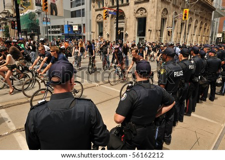 TORONTO-JUNE 27: Large number of Toronto police force blocks street to prevent 500 protesters on bicycles going close to G20 Convention Centre June 27, 2010 in Toronto. - stock photo