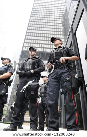 TORONTO-JUNE 27:  Police officers protecting an important financial building  during the G20 Protest on June 27, 2010 in Toronto, Canada.