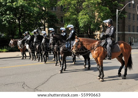 TORONTO-JUNE 25: Police on horseback restrict protesters movement away from G20 Summit at Convention Centre on June 25, 2010 in Toronto, Canada. - stock photo