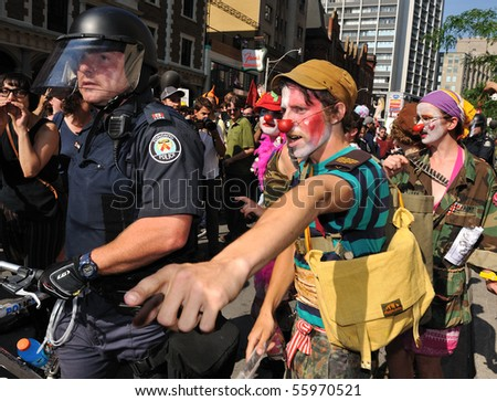 TORONTO-JUNE 25: Protester dressed as clown makes a point to policemen at G20 Protest on June 25, 2010 in Toronto, Canada. - stock photo