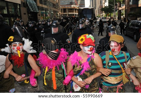 TORONTO-JUNE 25: Protesters dressed as clowns makes a shield in front of the police at G20 protest on June 25, 2010 in Toronto, Canada. - stock photo