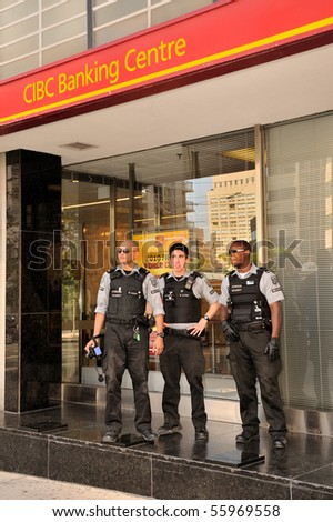 TORONTO-JUNE 25: Security service personnel in front of CIBC Bank at G20 protest on June 25, 2010 in Toronto, Canada. - stock photo