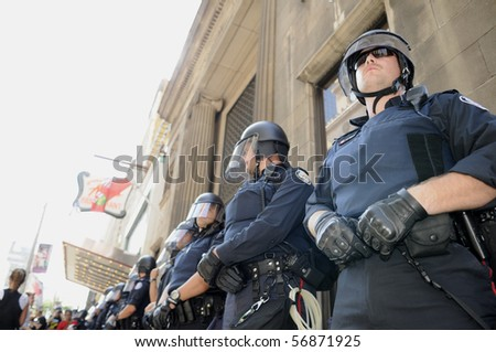TORONTO-JUNE 25:  Toronto Police officers in riot gear protecting  a financial building during the G20 Protest on June 25, 2010 in Toronto, Canada. - stock photo